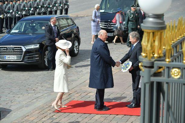 Kuningatar Sonjalla oli vaikeuksia pitää hatustaan huolta kovassa tuulessa.