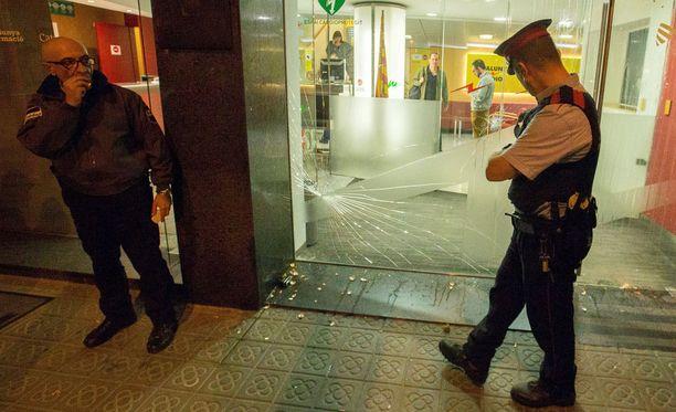 Katalonian paikallispoliisi katselemassa väkivallan jälkiä Catalunya Radio -radiokanavan toimituksen edessä. Journalistit joutuivat linnoittautumaan toimitukseensa perjantai-iltana, kun itsenäisyyden vastustajat yrittivät hyökätä sinne sisälle.