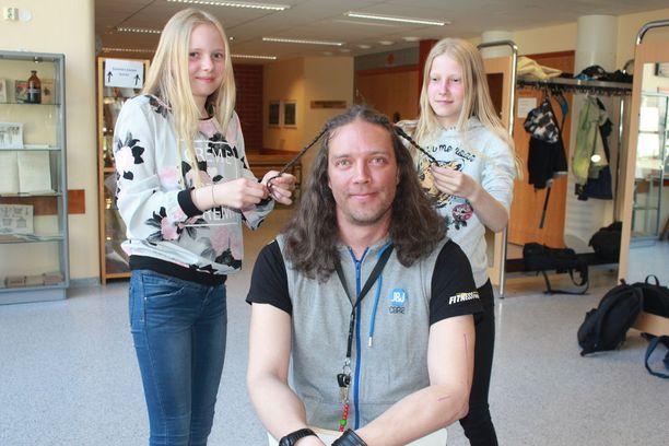 Kuudesluokkalaiset Minea Kivinen ja Edit Jokitalo letittivät Matti Savolan hiukset ennen leikkausta.