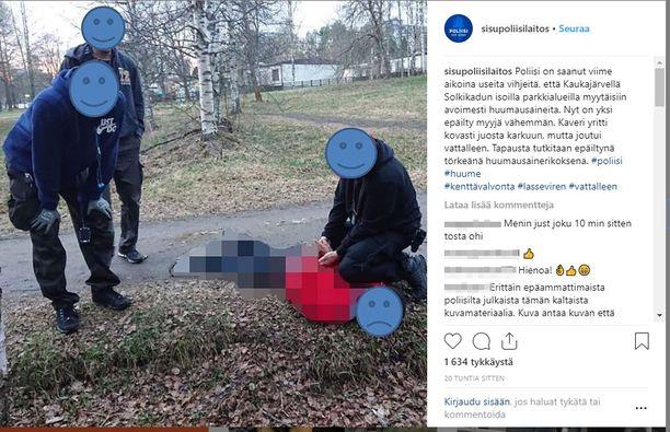 Poliisi julkaisi kuvan tilanteesta, jossa huumeiden myymisestä epäilty henkilö on taltutettu maahan. Ympärillä seisoo kolme poliisia. Kasvot on peitetty hymynaamoilla.