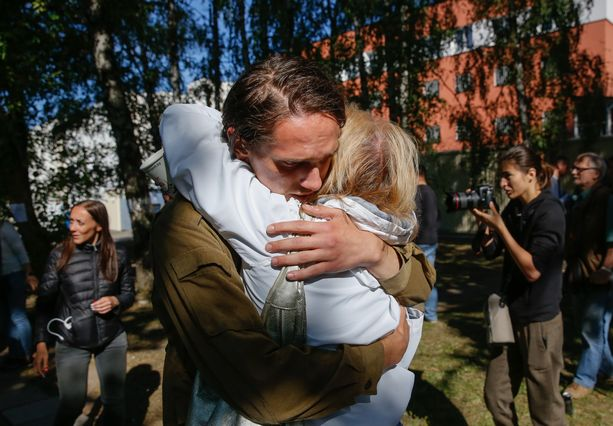 Sukulaiset ja ystävät halasivat perjantaina vapautuneita omaisiaan pidätyskeskuksen ulkopuolella Minskissä.