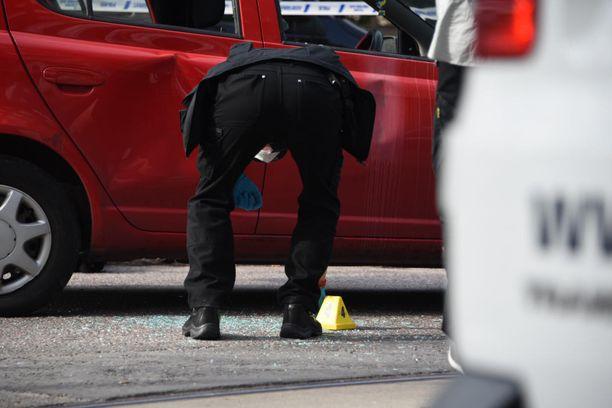 Rikostutkija poimi hylsyn läheltä punaista Toyotaa. Kuvassa näkyy myös murskaantunutta ikkunalasia. Havainnon mukaan ampuja hajotti ikkunan muuten kuin ampumalla.
