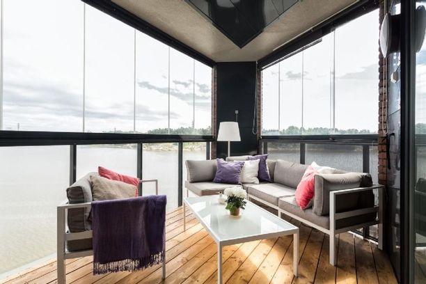 Tämän parvekkeen vetonaula ovat komeat maisemat ja suuret ikkunat. Kevytrakenteiset sohva ja pöytä sopivat pieneen tilaan eivätkä vie huomiota pois tärkeimmäistä.