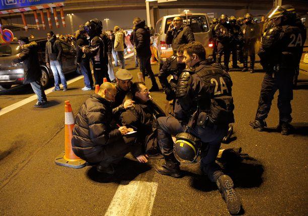 Loukkaantunutta taksikuskia hoidettiin Orlyn lentokentällä sen jälkeen kun bussikuski oli ajanut väkisin mielenosoittajien läpi.