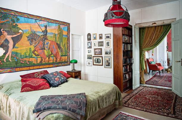 Kirjasto toimii myös vierashuoneena. Sängyn vieressä on vanhoja valokuvia sukulaisista. Tuulia kutsuu kokoelmaa kauhugalleriaksi, koska ennen kuvissa poseerattiin vakavina.