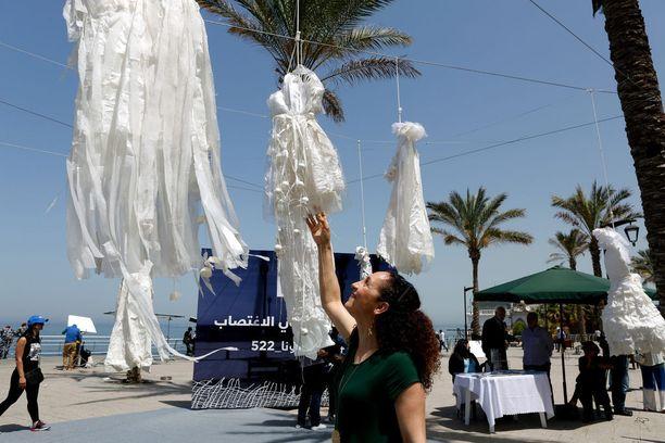 Libanonilainen aktivisti katselee taideteosta, jossa roikkuu hääpukuja. Teos on ilmaus maan rikoslakia vastaan.