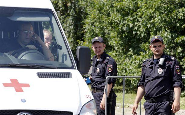Venäläispoliisit seisoivat kesäkuussa ruumishuoneen edustalla, mihin veneonnettomuudessa hukkuneiden lasten ruumiit kuljetettiin.