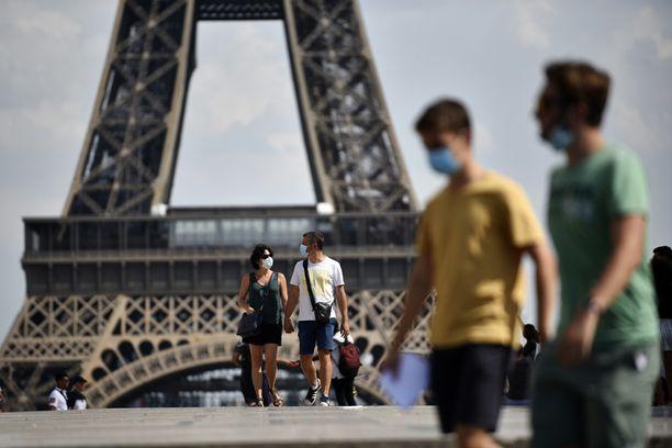 Joissain osissa Pariisia kasvomaskin käyttäminen tulipakolliseksi maanantaina. Kasvomaskia käyttäviä ihmisiä Eiffelin tornin edessä.