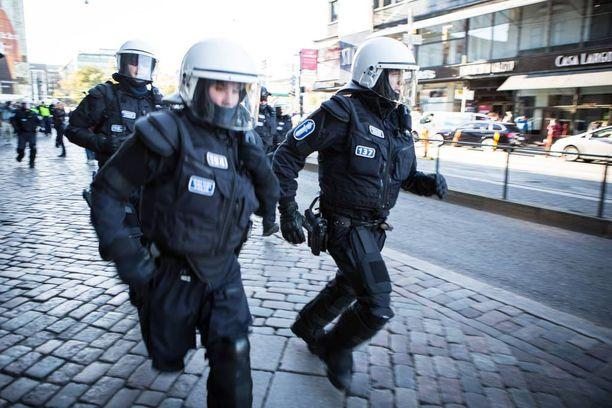 Mellakkavarusteiset poliisi joutuivat juoksemaan saadakseen mielenosoittajien kärkijoukon kiinni.
