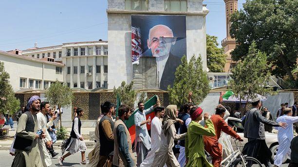 Itsenäisyyspäivän juhlijoita marssimassa Afganistanin presidentin Ashraf Ghanin julisteen ohi Kabulissa torstaina.