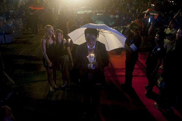 Ihmiset rukoilivat uhrien muistolle Khao Lakin muistotilaisuudessa.
