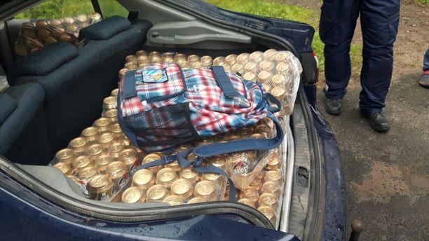 Matkalaukku oli kätketty auton takaluukkuun olutlaatikoiden alle.