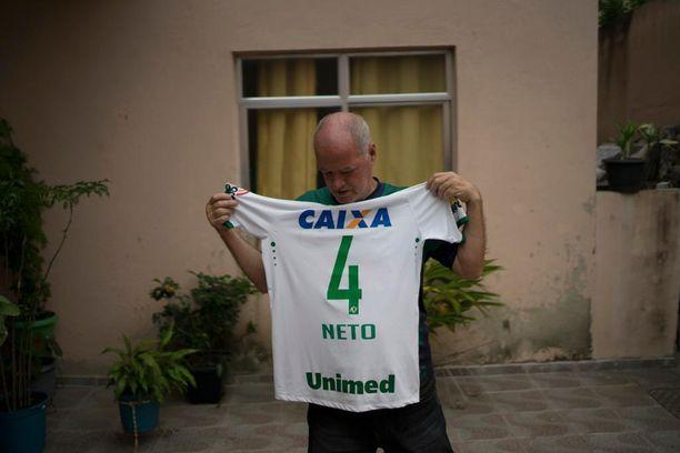 Helam Marinho Zampier esitteli poikansa Neton pelipaitaa Rio de Janeirossa. Hän pyytää ihmisiä rukoilemaan poikansa puolesta.