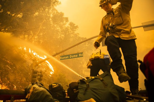 Kuvassa pelastustyöntekijät yrittivät pitää liekkejä kurissa estääkseen palon leviämisen Malibussa perjantaina 9.11.2018.
