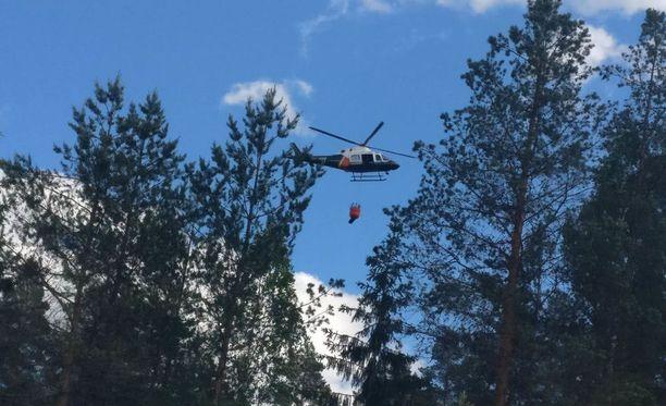 Rajavartioston helikopteri auttaa sammutustöissä.