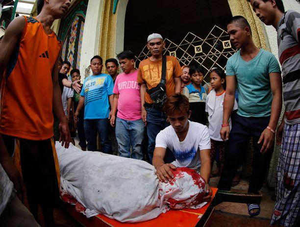 Sukulaiset surivat väitetyn huumekauppiaan ruumiin äärellä Manilassa perjantaina.