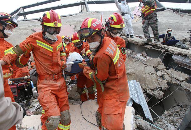Pelastajat kantoivat pois loukkaantunutta hotellin raunioista.