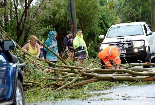 Ihmiset siirsivät kaatunutta puuta tieltä Yeppoonissa.