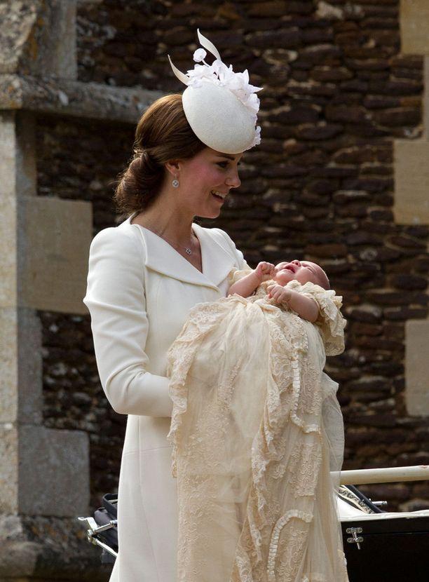 Catherine oli pukeutunut eleganttiin valkoiseen pukuun, jonka katseenvangitsija oli erikoinen päähine. Prinsessa Charlotte alkoi itkeä, kun Catherine nosti tämän syliinsä kirkon pihassa.