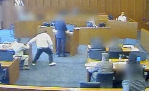 Angilou nousee oikeussalissa paikaltaan ja nappaa kynän, jolla käy todistajan kimppuun.