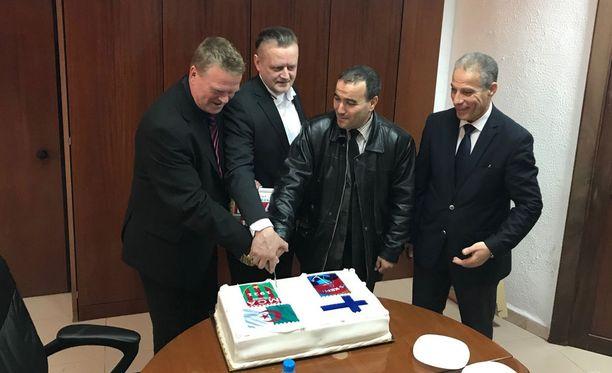PS Kemin delegaation Juha Nykänen (vas.) ja Antti Pasanen leikkaavat kakkua yhdessä MCA:n edustajien kanssa.