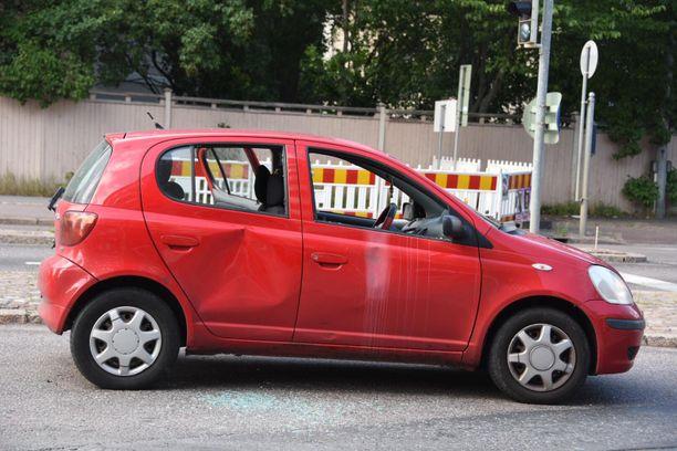 Ammuttu punainen henkilöauto jäi sijoilleen keskelle risteystä.