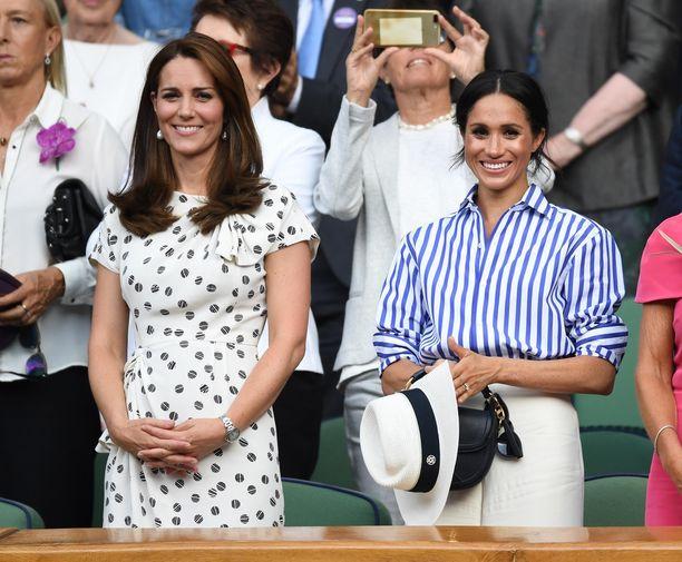 Herttuattaret Catherine ja Meghan rinnakkain Wimbledonin tennisottelussa. Pituuseron huomaa selvästi.