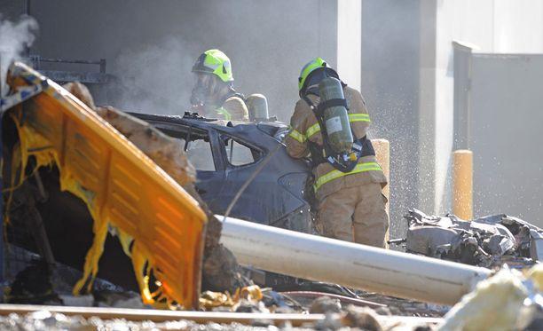 Pelastustyöntekijöitä onnettomuuspaikalla. Viiden ihmisen uskotaan olleen onnettomuushetkellä pienkoneen kyydissä.