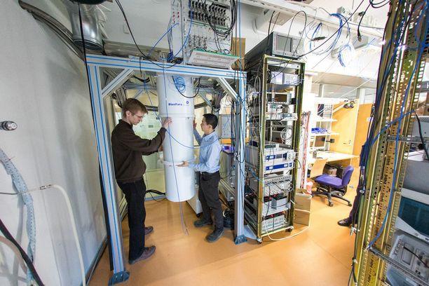 Matti Partanen (vas.) ja Kuan Yen Tan avaavat kuvassa kryostaattia eli superpakastinta, jolla kvanttilaitteen ja kvanttipiirijäähdyttimen sisältävä piisiru jäähdytetään lähelle absoluuttista nollapistettä.