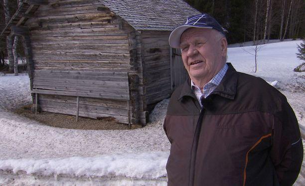 Veikko Juntunen seisoo piha-aitan edessä. Sinne neuvostopartisaanit surmasivat jatkosodassa hänen äitinsä ja vanhemman veljensä.