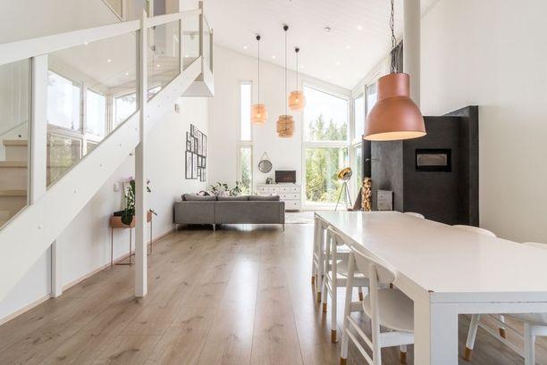 Tumman talon sisältä paljastuu moderni ja vaalea sisustus.