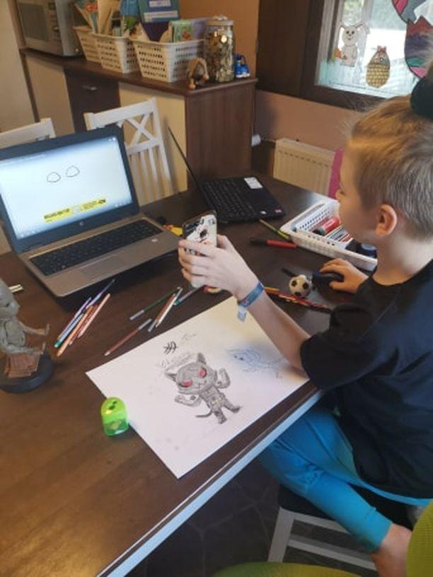 Tiitus esittelee isälle nettivideon avulla tekemiään piirroksia videopuhelun välityksellä.