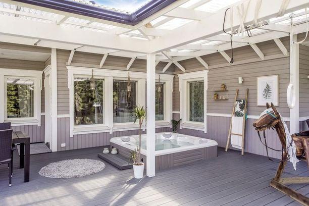Osittain katetulla terassilla on poreallas, ja terassi on sisustettu kotoisasti.