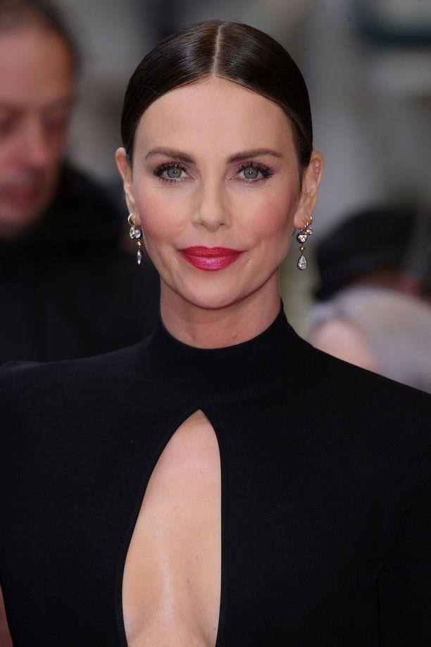 Charlize Theronin fuksiaan vivahtava huulipuna tekee lookista raikkaan oloisen.