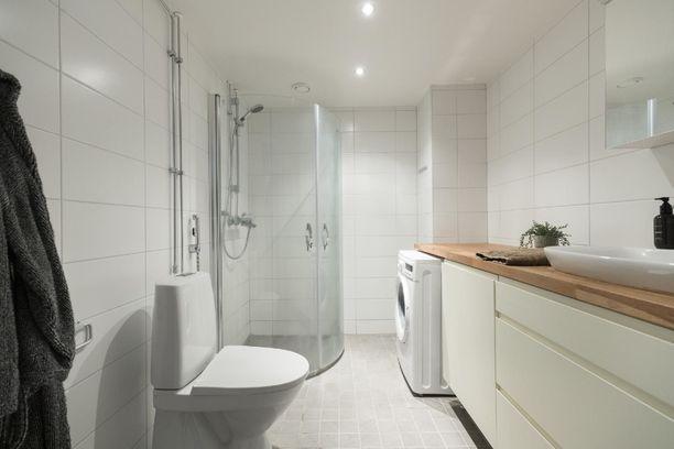 Pitkulaisessa kylpyhuoneessa on hyvät säilytystilat ja tasot.