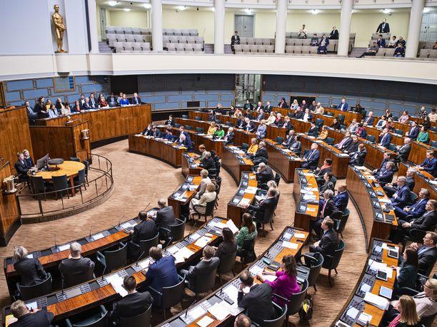 Maaliskuisessa arkistokuvassa kansanedustajat ja ministerit istuivat vielä vierekkäin. Nyt eduskunnan koronavirusohjeet ovat vähentäneet ministereiden ja kansanedustajien määrää istuntosalissa.