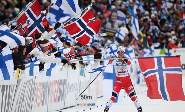 Marit Björgen hiihti viestivoittoon lippumeren keskellä.