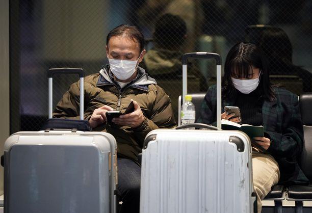 Matkustajat Tokion lentokentällä käyttävät hengityssuojaa.