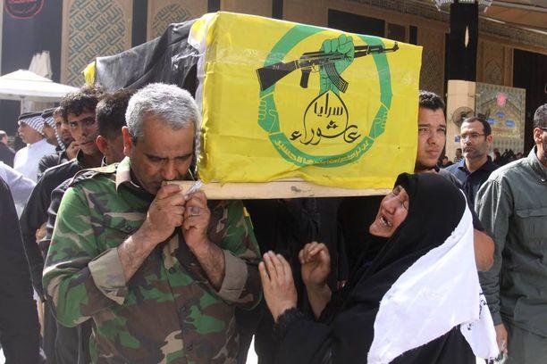 Nainen suri kaatuneen sotilaana arkun äärellä Najafissa lauantaina. Irakilaissotilas sai surmansa taistelussa Isisiä vastaan.