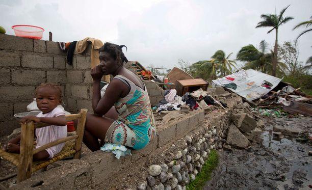 Nainen istui torstaina tyttärensä kanssa hurrikaanin runteleman kotinsa edessä.