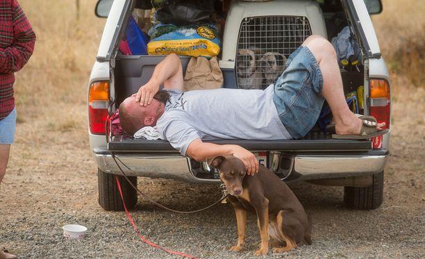 Mies lepäämässä evakuointialueella Kaliforniassa. Tuhannet ihmiset ovat joutuneet jättämään kotinsa tulipalojen vuoksi.