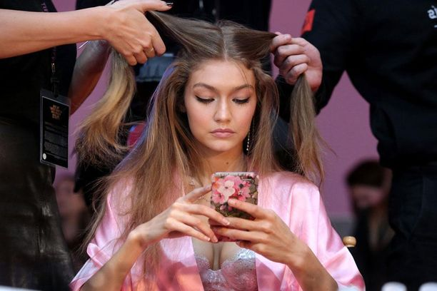 Gigi Hadid tappaa aikaa puhelimellaan samalla, kun hiustaiteilijat loihtivat hänen kampaustaan.