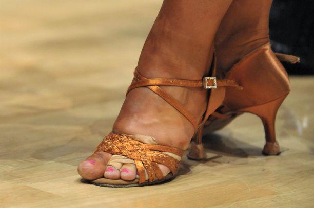 Naisen mukaan päkiään sattuu tanssiessa. Hänen pitää niin ikään ostaa eri parisia kenkiä. Kuvituskuva.
