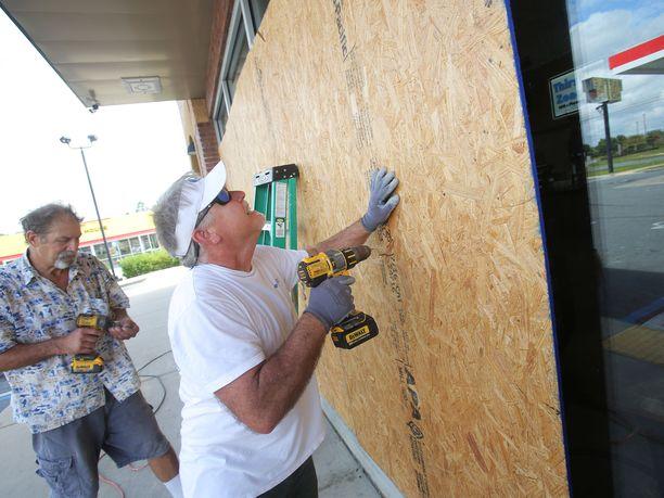 Mikes Jones (edessä) ja Dan Steele valmistelevat huoltoasemaansa hurrikaanin tuloon Panama Cityssä Floridassa