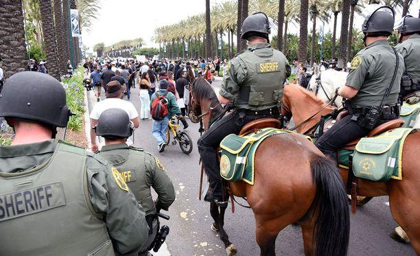 Mellakkavarusteiset poliisit ja ratsupoliisit valvoivat tiiviisti mielenosoittajien toimia.