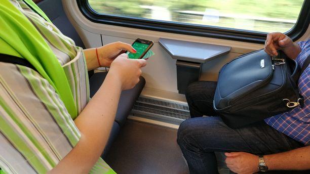Konduktöörit tarkastavat matkustajien junaliput mobiilisovelluksella.