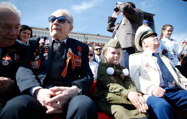 Veteraaneja ja lapsia Punaisella torilla voitonpäivän sotilasparaatin yleisössä.