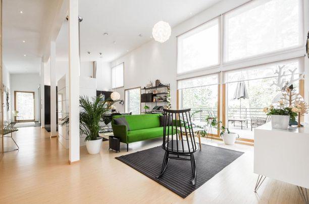 Olohuoneessa on lattiasta kattoon ulottuvat ikkunat ja valtava huonekorkeus.