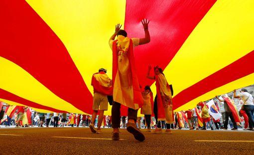 Ihmiset kävelevät valtavan Katalonian lipun alla kansallispäivänä Barcelonassa.