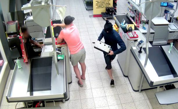 Kommandopipoon naamioitunut mies ryösti kassan Espoon Tuomarilassa teräaseella uhaten. Kuvan myyjä ja vaaleanpunaiseen paitaan pukeutunut mies ovat asiassa pelkästään todistajina, eikä heitä epäillä rikoksesta.